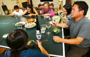 Charles Phan at home eating with his family.