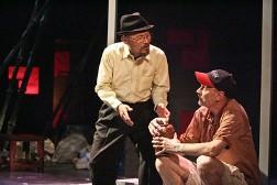 """Actors Long Nguyễn (standing) and Michael Krawic in 'Christmas in Hanoi.'"