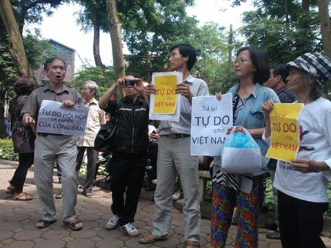 "Vietnamese hold up signs that say, ""Give Vietnam back its Freedom."""