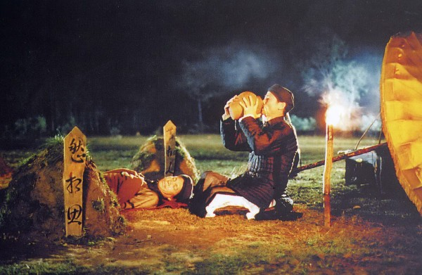 Master Nguyễn (right) has his last drink before setting fire to it all – his precious liquor jars stored in small mounds of earth, his loyal butler's dead body, himself, and an old way of life