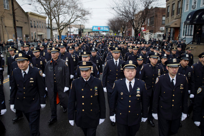 Police officers arrive to the funeral of New York Police Department Officer Wenjian Liu at Aievoli Funeral Home, Sunday, Jan. 4, 2015, in the Brooklyn borough of New York. Liu and his partner, officer Rafael Ramos, were killed Dec. 20 as they sat in their patrol car on a Brooklyn street. The shooter, Ismaaiyl Brinsley, later killed himself. (AP Photo/John Minchillo)
