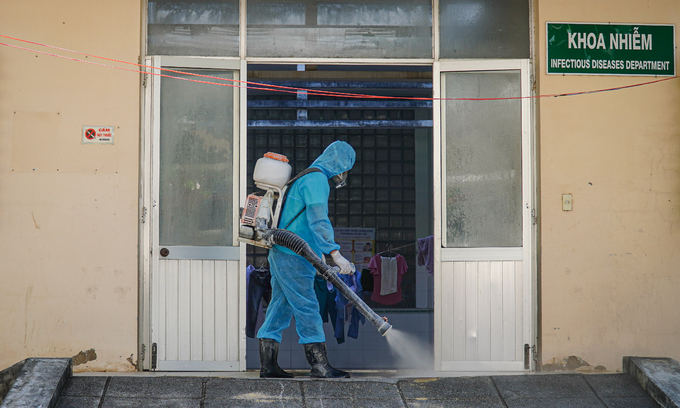 Medical staff disinfecting hospital entrance