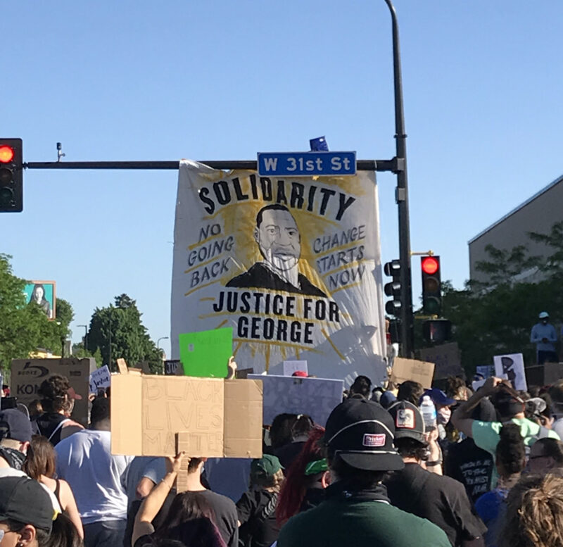 "Protestors marching down a street in Minneapolis. A banner hangs off the sign post for W 31st St. The banner shows a drawing of George Floyd and reads ""Solidarity,"" ""Justice for George,"" ""No Going Back,"" and ""Change Starts Now."""
