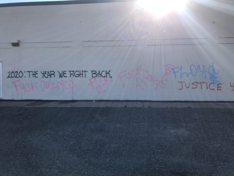 "Graffiti on the side of a white building that reads ""2020: The Year We Fight Back,"" ""Fuck America,"" ""Fuck [heart emjoi],"" ""Fuck the thruth,"" ""Floyd,"" and ""Justice"""